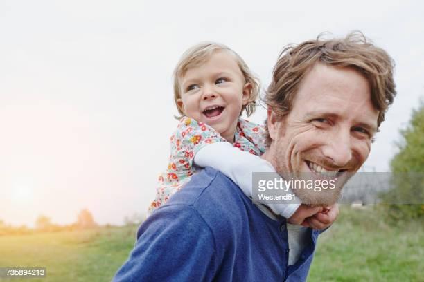 father carrying daughter piggyback - vater stock-fotos und bilder