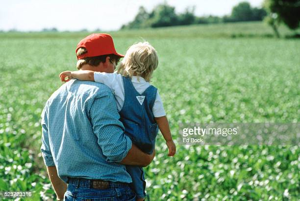 Father Carrying Daughter Through Field