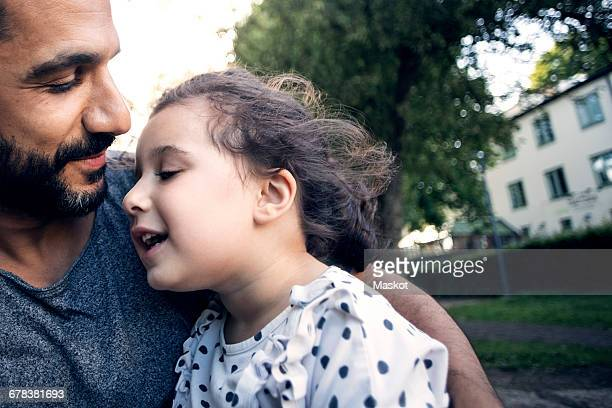 Father carrying daughter while sitting at park