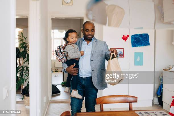 father carrying daughter with backpack while keeping paper bag on table at home - carrying stock pictures, royalty-free photos & images