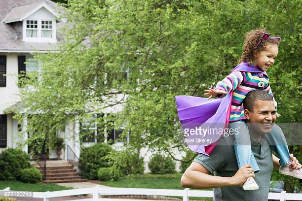 Father carrying flying superhero daughter