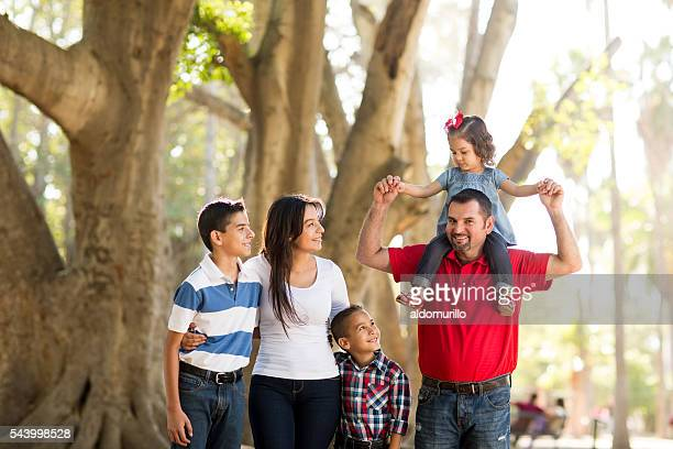 Father carrying girl on shoulders with family