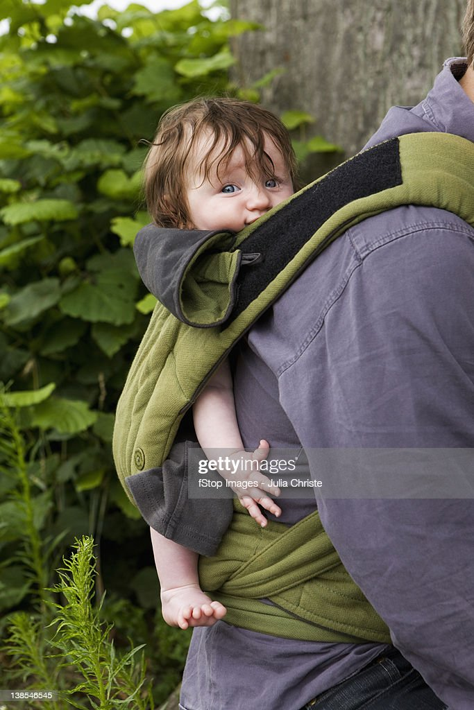 A father carrying his baby daughter in baby carrier, focus on baby : Stock Photo
