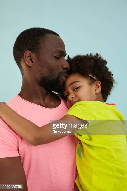 father carrying his daughter against a pale blue background - nerys jones stock photos and pictures