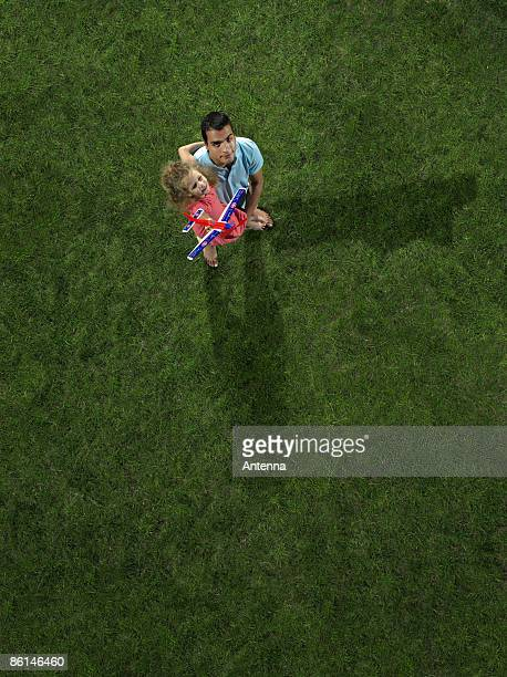 A father carrying his daughter holding a toy airplane
