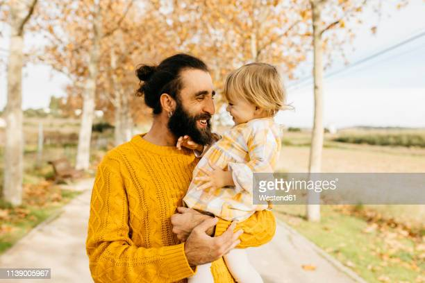 father carrying his daughter on a morning day in the park in autumn - yellow dress stock pictures, royalty-free photos & images