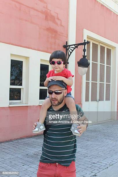 father carrying his little daughter on shoulders - leanintogether stock pictures, royalty-free photos & images