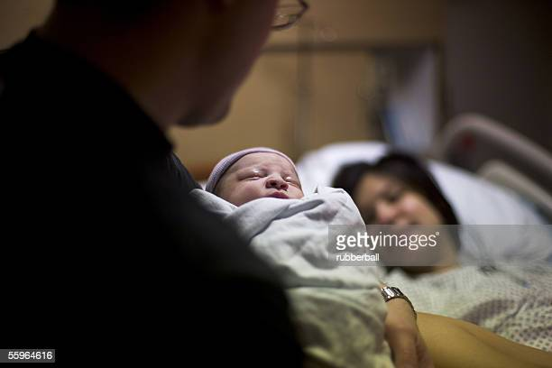 Father carrying his newborn baby girl with his wife lying on a bed