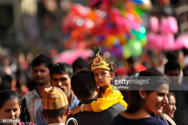 A Father carrying his son impersonate as Lord Krishna during Krishna Janmashtami Festival celebrated at Patan Nepal on Monday August 14 2017 Krishna...