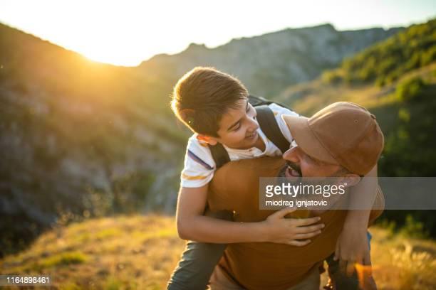padre che porta suo figlio sulla cima della collina - portare a cavalluccio foto e immagini stock