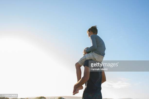 father carrying his son on his shoulders on the - schulter stock-fotos und bilder