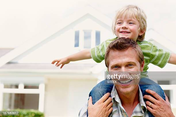Father carrying his son on shoulders in front of house