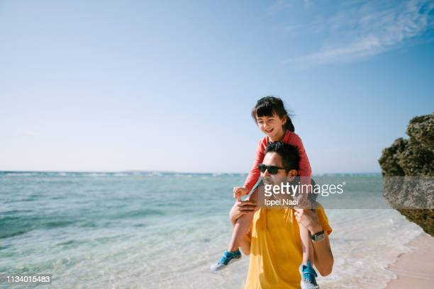 father carrying little girl on shoulders on tropical beach, okinawa, japan - travel and not business stock photos and pictures