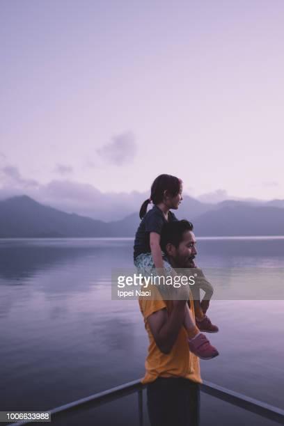 Father carrying little girl piggyback at twilight, Nikko, Japan