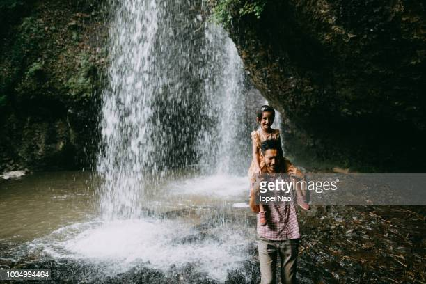 Father carrying little girl piggyback under waterfall, Japan