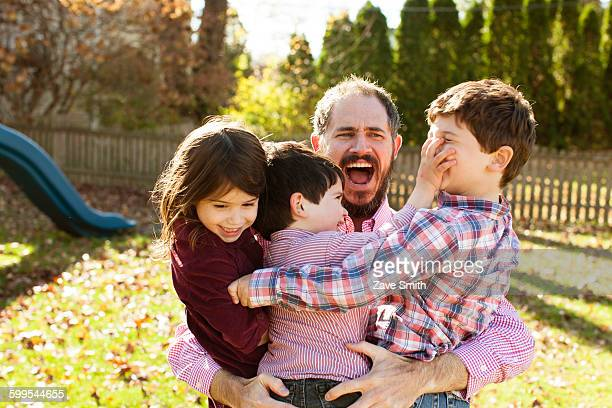 Father carrying playful children in his arms, open mouthed looking surprised