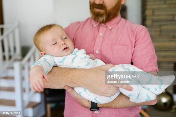 father carrying sleeping baby son (6-11 months ) - 6 11 months stock pictures, royalty-free photos & images