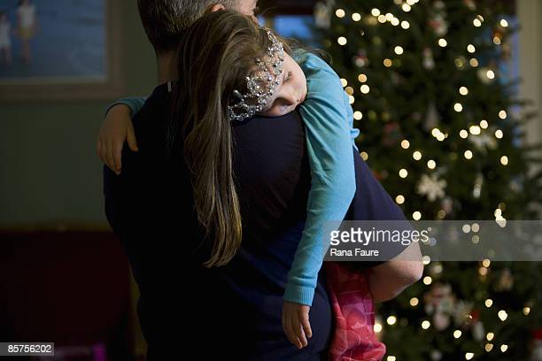 father carrying sleeping daughter at christmas - carrying imagens e fotografias de stock