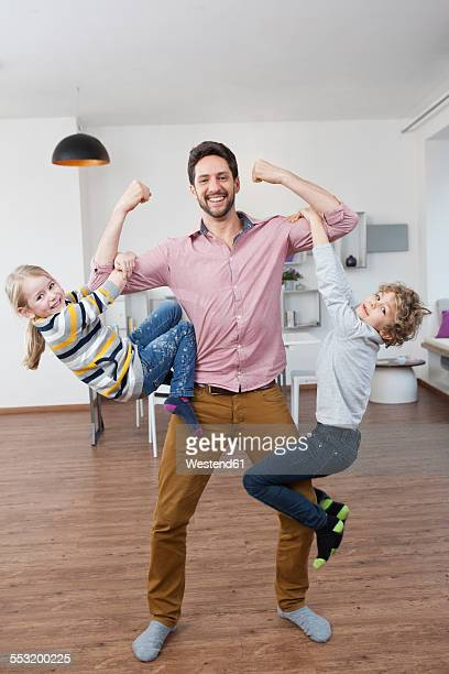 Father carrying son and daughter on his arms