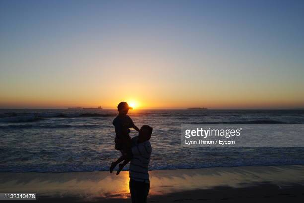 father carrying son at beach against sky during sunset - lynn pleasant stock pictures, royalty-free photos & images