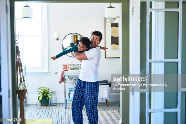 father carrying son in bathroom - candid stock pictures, royalty-free photos & images