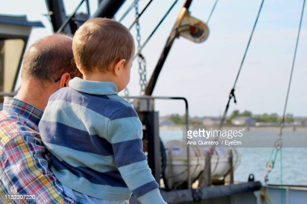 Father Carrying Son On Boat In Sea