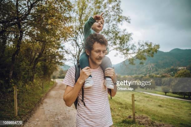 padre a hijo que lleva en sus hombros - masculinidad moderna fotografías e imágenes de stock