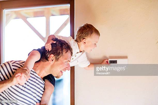Father carrying son on shoulders, adjusting thermostat