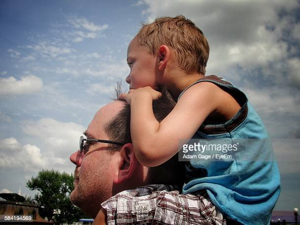 Father Carrying Son On Shoulders Against Cloudy Sky
