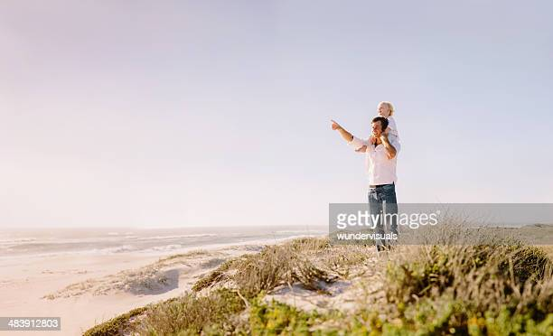 Father carrying son on shoulders at beach