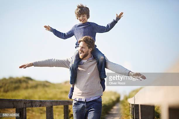 Father carrying son on shoulders at the coast