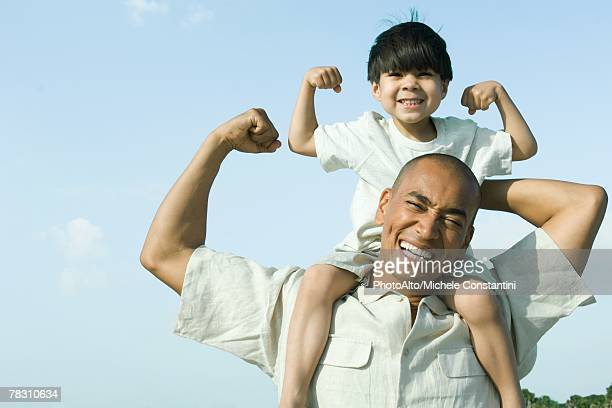 father carrying son on shoulders, both flexing arm muscles and smiling at camera - flexing muscles stock pictures, royalty-free photos & images