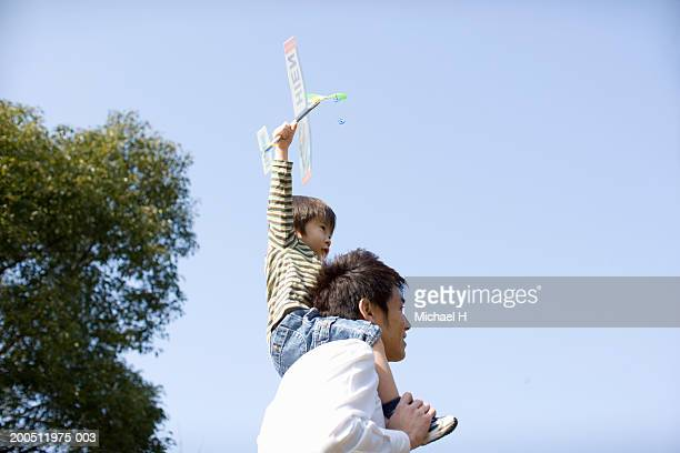 Father carrying son (2-4) on shoulders, boy holding toy airplane