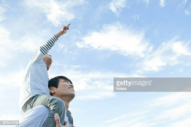 father carrying son(4-5) on shoulders, looking up - carrying a person on shoulders stock photos and pictures