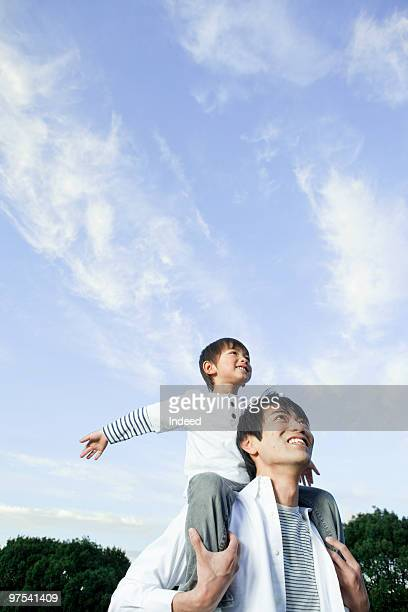 Father carrying son on shoulders, low angle view