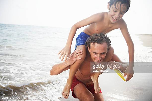 Father carrying son (8-10) on shoulders on beach, smiling