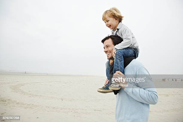 father carrying son on shoulders - shoulder stock pictures, royalty-free photos & images