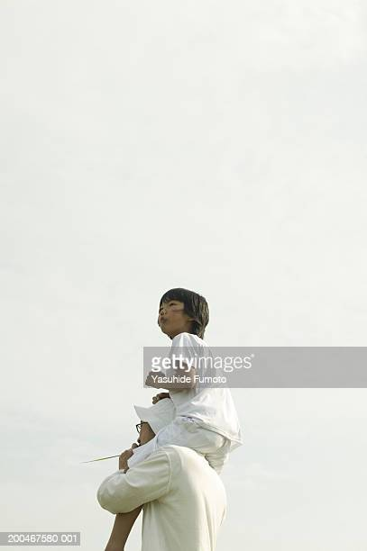 father carrying son (9-11) on shoulders, side view - carrying a person on shoulders stock photos and pictures