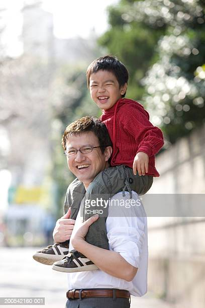 father carrying son (4-6) on shoulders, smiling, side view - 45 49歳 ストックフォトと画像