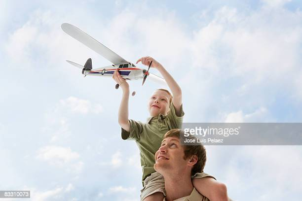 Father carrying son on shoulders while playing wit