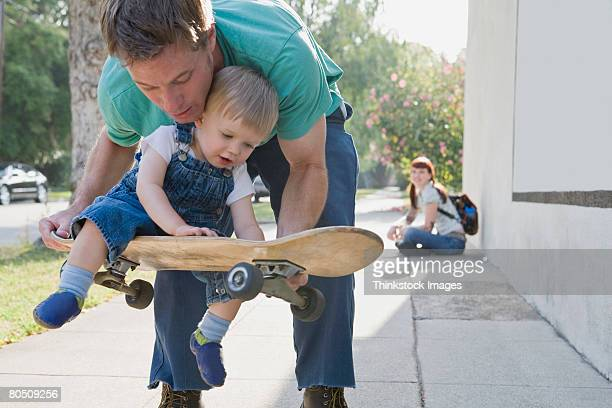 Father carrying son on skateboard