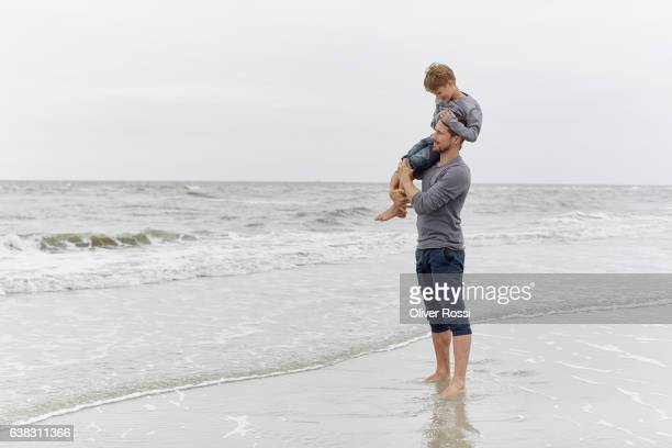 Father carrying son on the beach