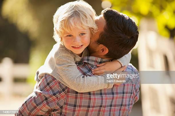 Padre llevando hijo al aire libre