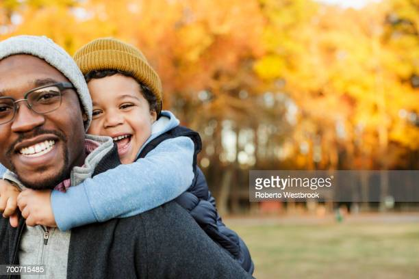 father carrying son piggyback in park - african american family home stock photos and pictures