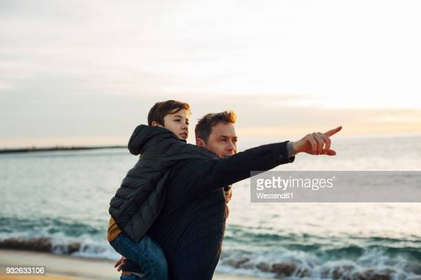 father carrying son piggyback on the beach at sunset pointing finger - sohn stock-fotos und bilder