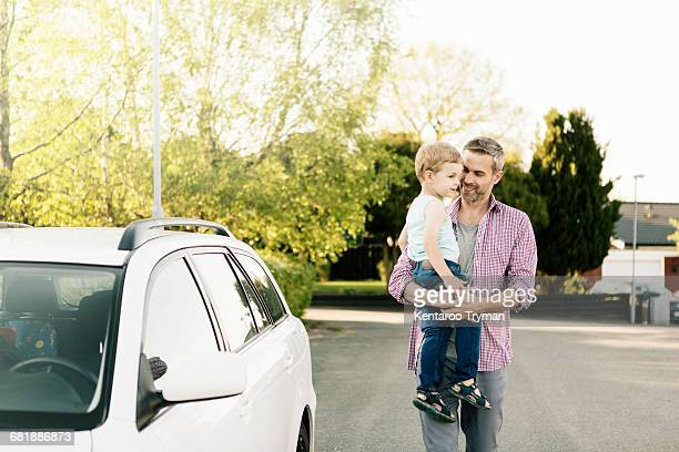 Father carrying son while walking by car on street