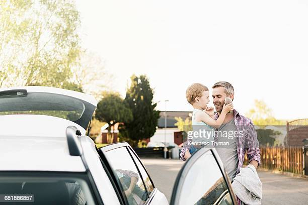 father carrying son with stuffed toy while standing by car on street - white boot stock pictures, royalty-free photos & images