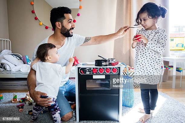father carrying toddler while playing with daughter in bedroom at home - dreiviertelansicht stock-fotos und bilder