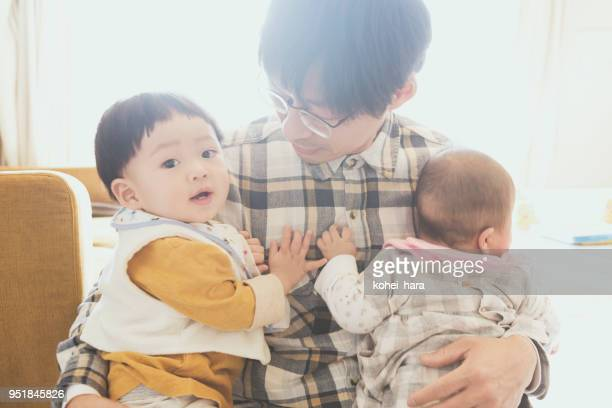 father carrying two babies at home - modern manhood stock pictures, royalty-free photos & images