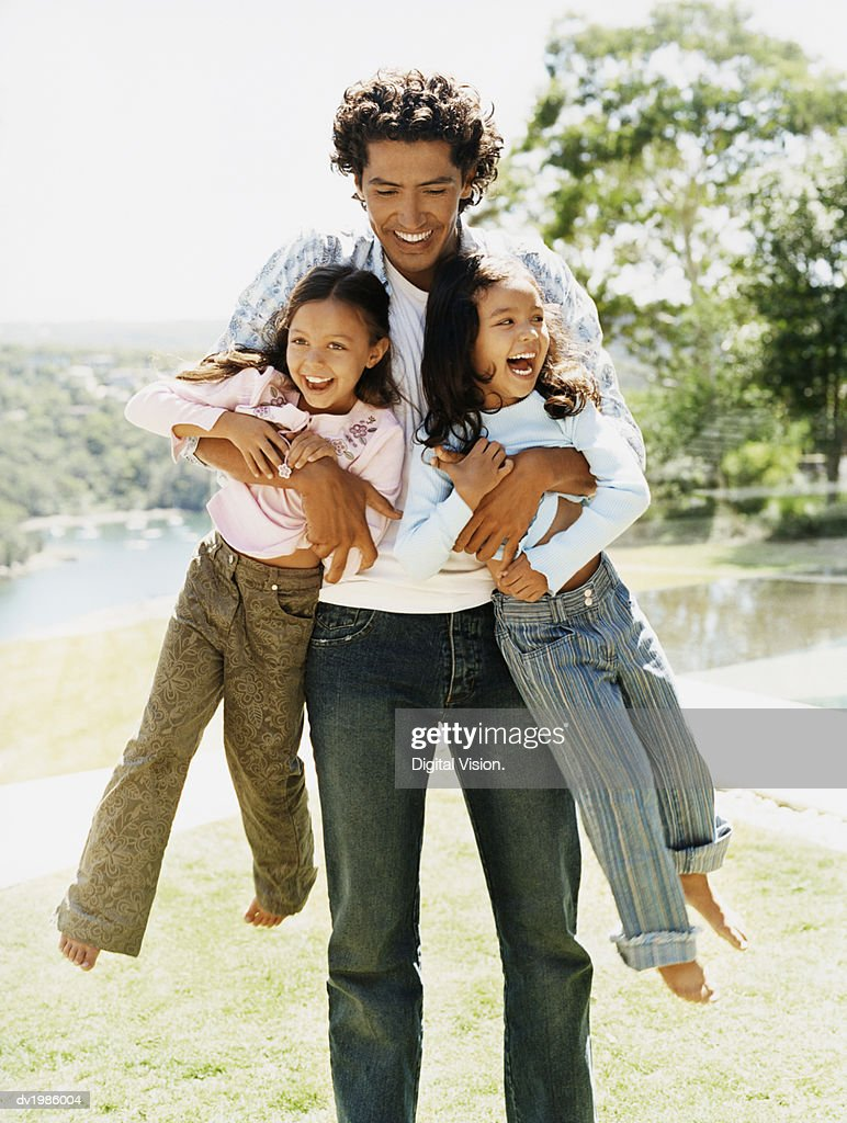 Father Carrying Two Daughters : Stock Photo
